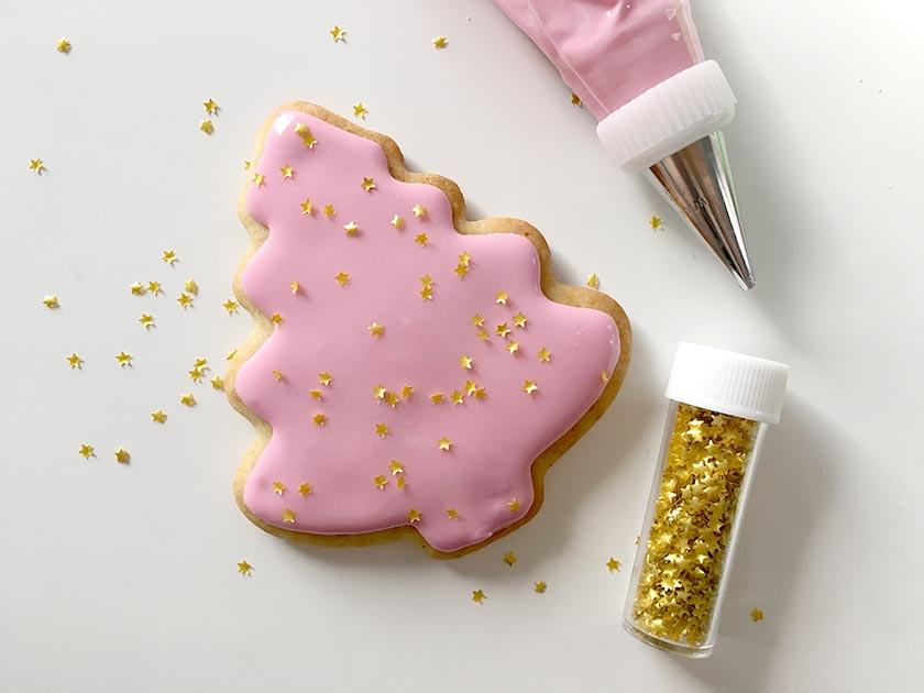 7 cover a tree cookie with pink royal icing sprinkle wilton gold star edible accents over the icing while it is still wet